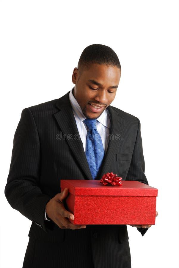 Homme d'affaires d'Afro-américain retenant un cadeau images stock