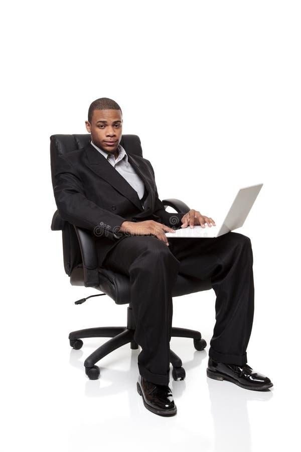 Homme d'affaires d'Afro-américain s'asseyant avec l'ordinateur portatif image libre de droits