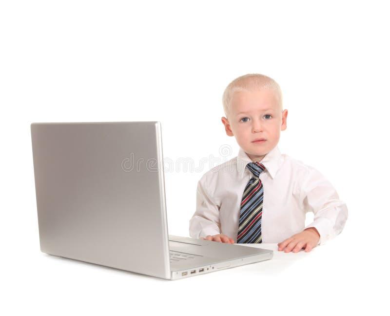 Homme d'affaires d'enfant travaillant sur un ordinateur portable photographie stock