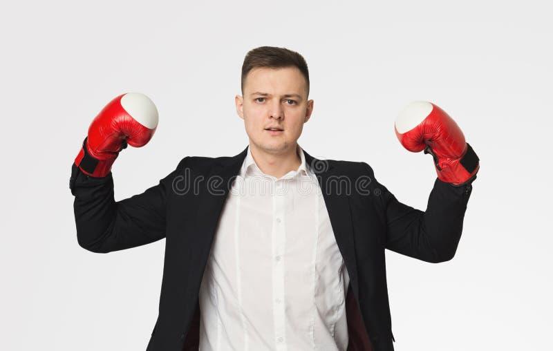 Homme d'affaires dans des gants de boxe fléchissant des biceps images stock