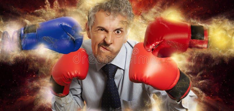 Homme d'affaires dans des gants de boxe sur le noir image libre de droits