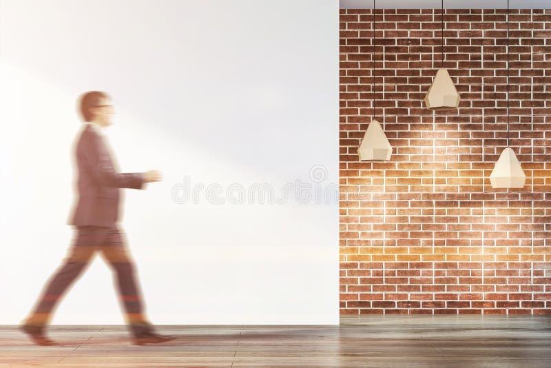 Homme d'affaires dans l'intérieur vide de pièce de blanc et de brique photo libre de droits
