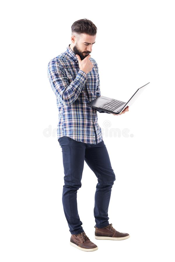 Homme d'affaires dans l'ordinateur portable se tenant et de observation de chemise de plaid pensant avec la main sur la barbe images stock