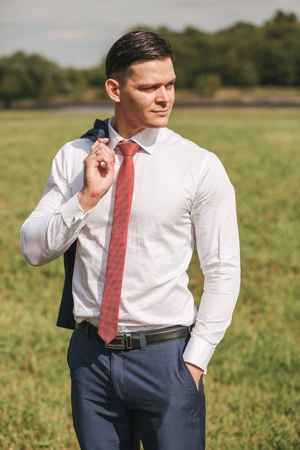 Homme d'affaires dans la chemise blanche et le lien rouge se tenant sur l'herbe verte photographie stock libre de droits