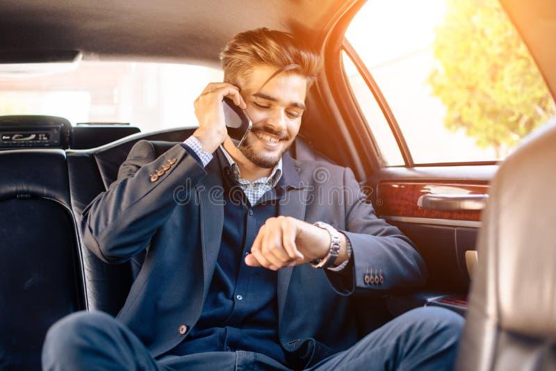 Homme d'affaires dans la limousine, vérifiant sa montre photo stock