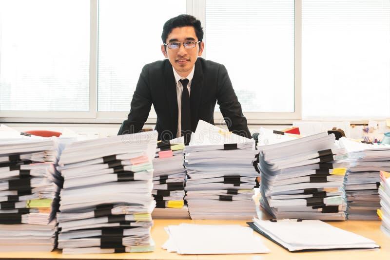 Homme d'affaires dans la position de costume dans le bureau avec la pile des documents sur le premier plan photo libre de droits