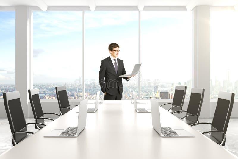 Homme d'affaires dans la salle de conférence moderne avec des meubles, ordinateurs portables image stock