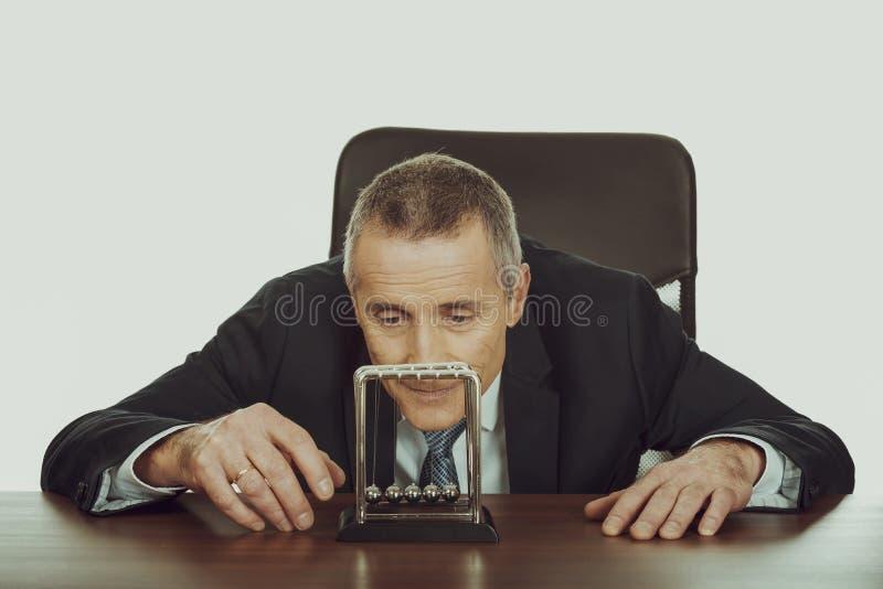 Homme d'affaires dans le bureau jouant avec des boules de newton photographie stock