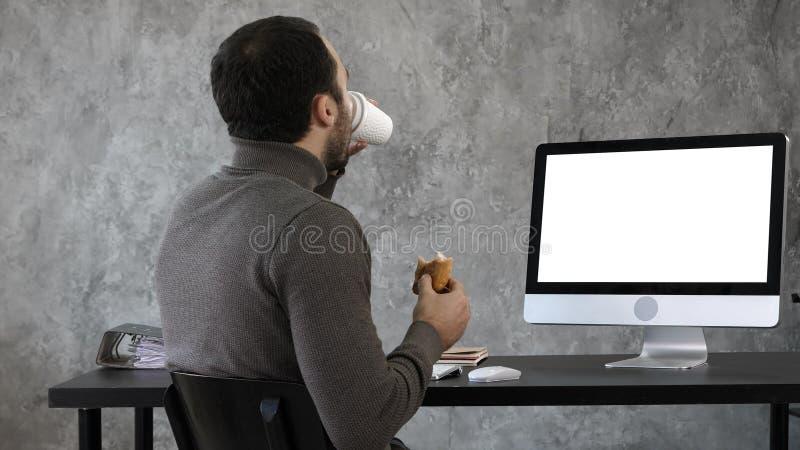 Homme d'affaires dans le bureau prenant le petit déjeuner, déjeuner et observant quelque chose sur l'imper, ordinateur Affichage  image libre de droits