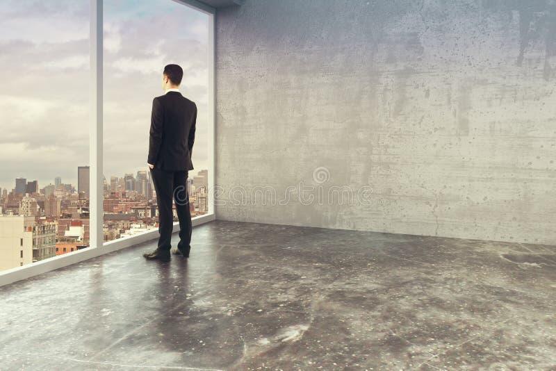 Homme d'affaires dans le bureau vide de style de grenier avec des fenêtres dans le plancher photo libre de droits