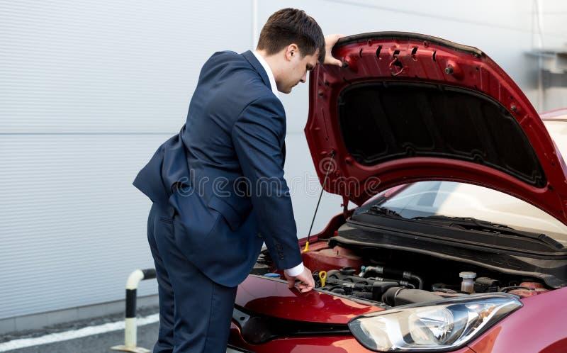 Homme d'affaires dans le capot d'ouverture de costume de la voiture ouverte images stock