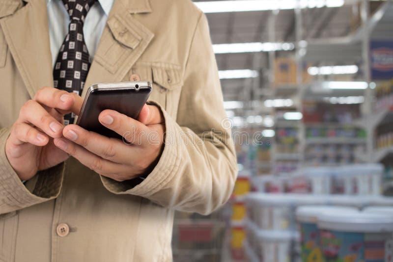 Homme d'affaires dans le centre commercial utilisant le téléphone portable photo libre de droits