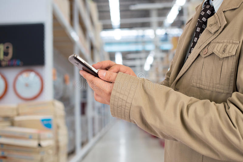 Homme d'affaires dans le centre commercial utilisant le téléphone portable photo stock