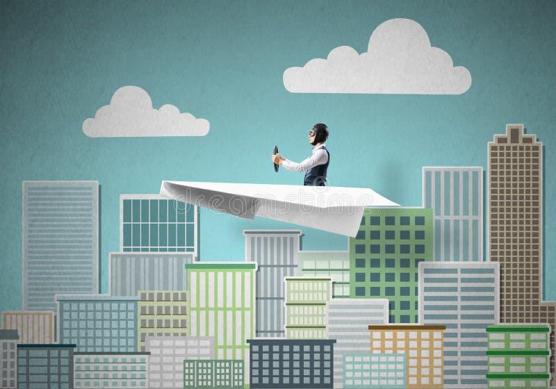 Homme d'affaires dans le chapeau d'aviateur se reposant dans l'avion de papier photographie stock libre de droits