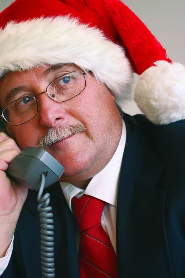 Homme d'affaires dans le chapeau de Santa parlant au téléphone image libre de droits