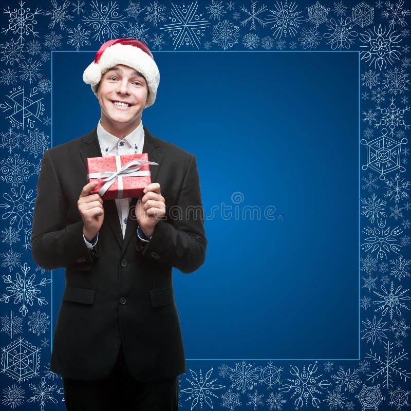 Homme d'affaires dans le chapeau de Santa tenant le cadeau photos libres de droits
