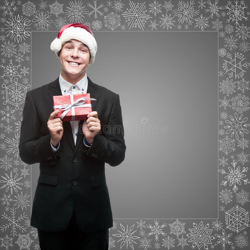 Homme d'affaires dans le chapeau de Santa tenant le cadeau photo libre de droits