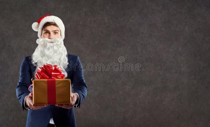 Homme d'affaires dans le costume de Santa Claus avec un cadeau dans sa main photo libre de droits