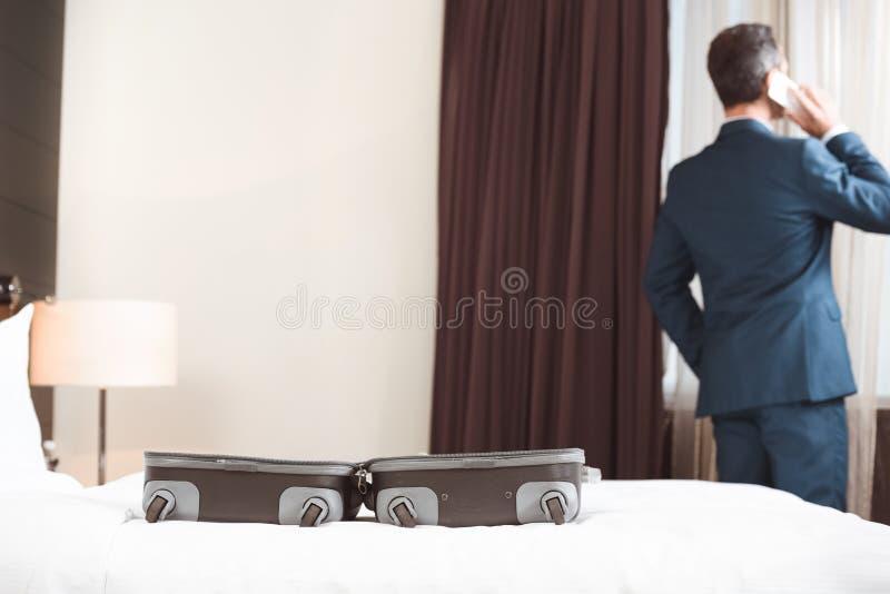 Homme d'affaires dans le costume formel parlant au téléphone dans la chambre d'hôtel avec la valise ouverte photo stock