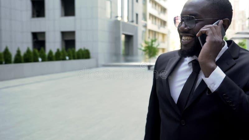 Homme d'affaires dans le costume marchant près du centre d'affaires, parlant au téléphone, réussi photos stock