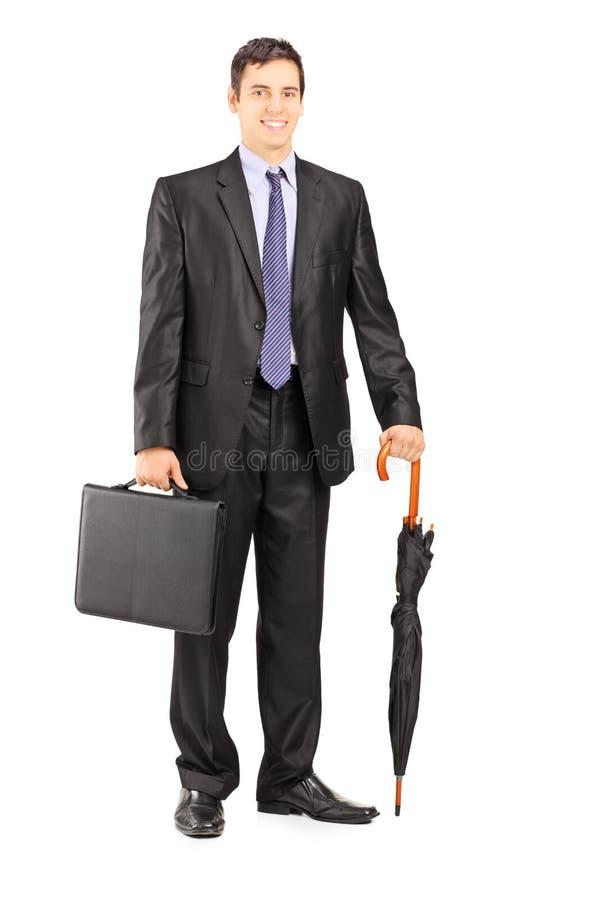 Homme d'affaires dans le costume noir tenant un parapluie et une serviette photographie stock libre de droits