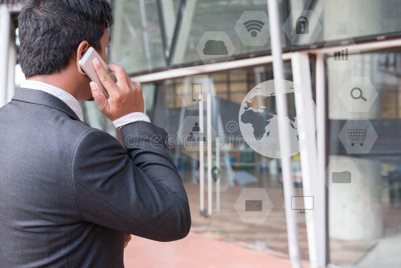 Homme d'affaires dans le costume parlant au téléphone intelligent tout en tenant l'outsid images stock