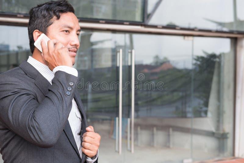 Homme d'affaires dans le costume parlant au téléphone intelligent tout en tenant l'outsid photographie stock libre de droits