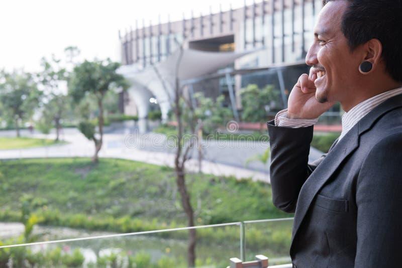 Homme d'affaires dans le costume parlant au téléphone intelligent tout en tenant l'outsid photographie stock