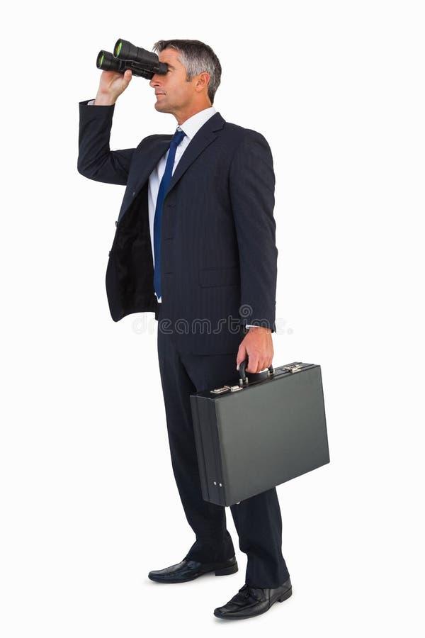 Homme d'affaires dans le costume regardant par des jumelles photos libres de droits