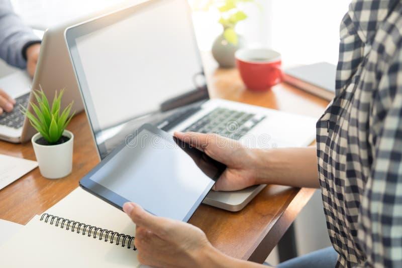 Homme d'affaires dans le costume se reposant à la table travaillant à son ordinateur portable et regardant un document sur le bur photographie stock libre de droits
