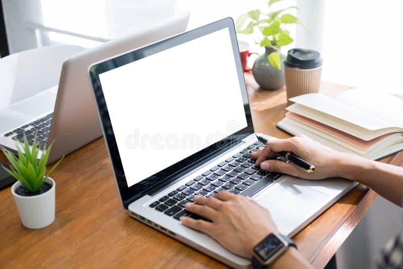Homme d'affaires dans le costume se reposant ? la table travaillant ? son ordinateur portable et regardant un document sur le bur photographie stock