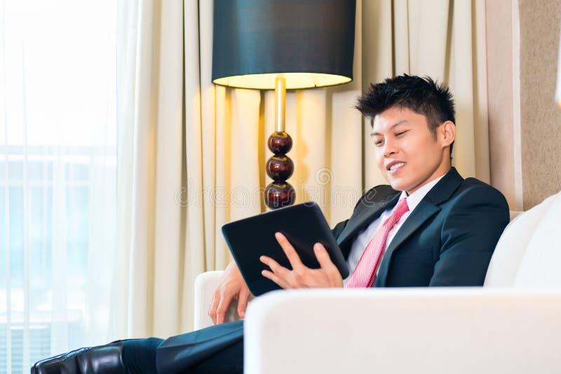 Homme d'affaires dans le fonctionnement asiatique de chambre d'hôtel photos libres de droits