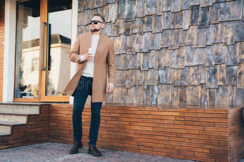 Homme d'affaires dans le manteau, les lunettes de soleil et la tasse de café bruns dans des ses mains posant sur le fond de café, photographie stock libre de droits