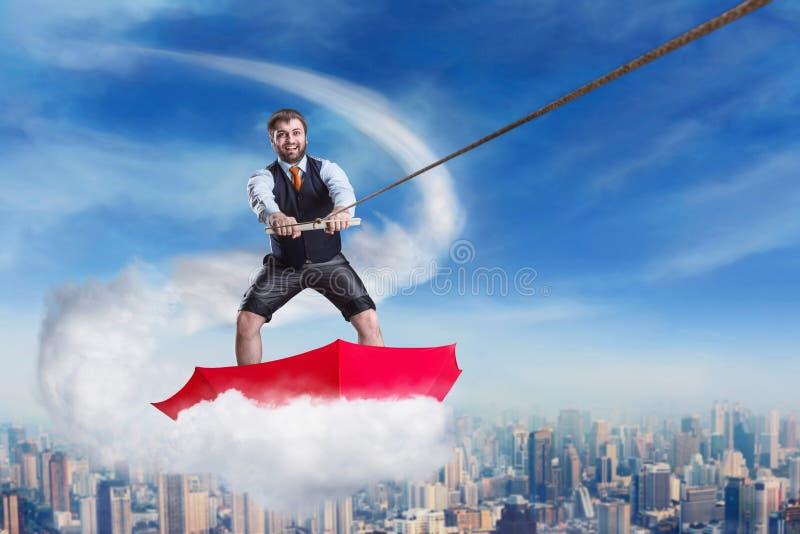 Homme d'affaires dans le parapluie sur le nuage image stock