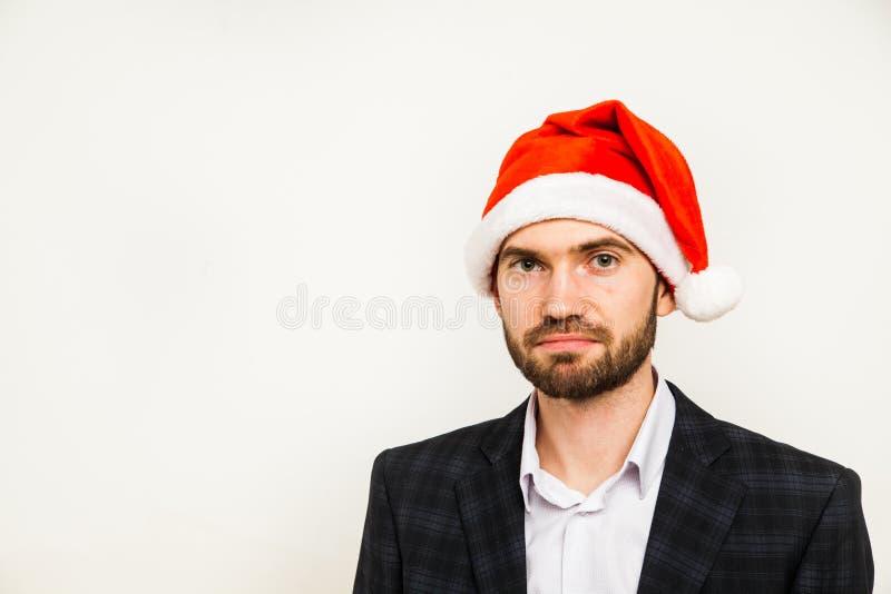 Homme d'affaires dans le procès avec le chapeau de Santa sur la tête D'isolement au-dessus du fond blanc images libres de droits