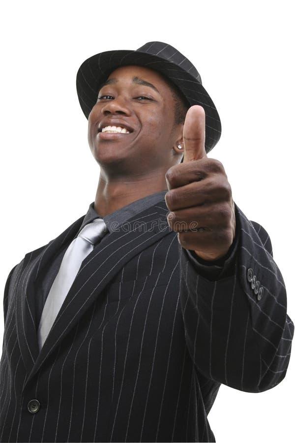 Homme d'affaires dans le procès et chapeau renonçant aux pouces image stock