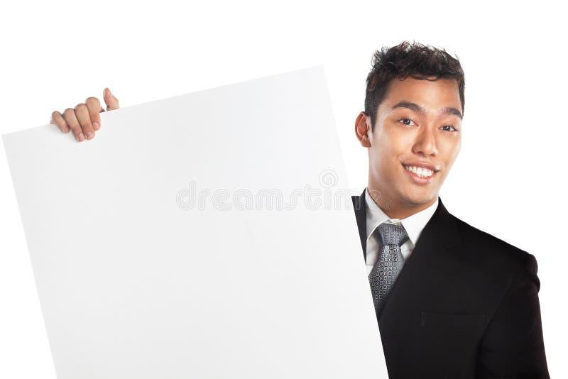 Homme d'affaires dans le procès retenant le signe blanc, plaquette photo libre de droits