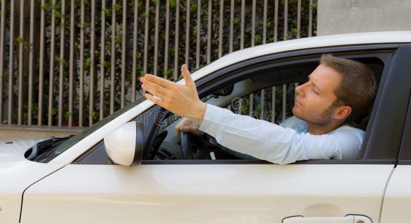Homme d'affaires dans sa voiture faisant un geste photo stock