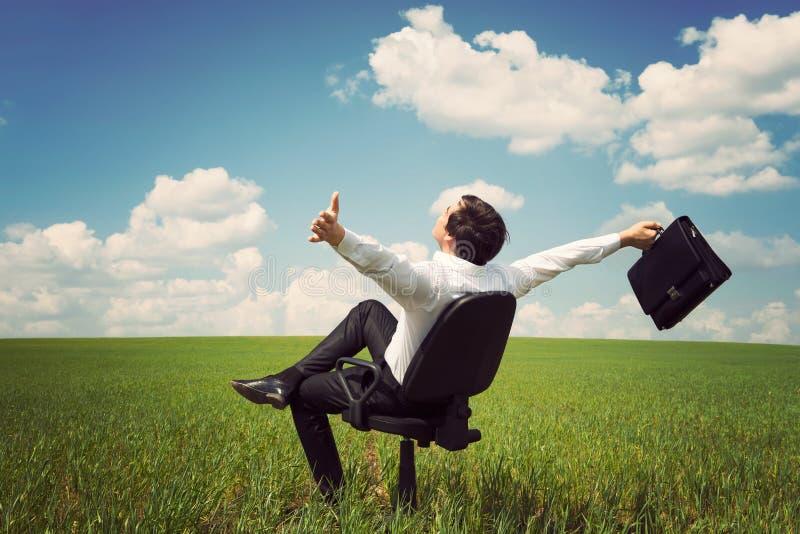 Homme d'affaires dans un domaine avec un ciel bleu se reposant sur un bureau Chai photographie stock libre de droits