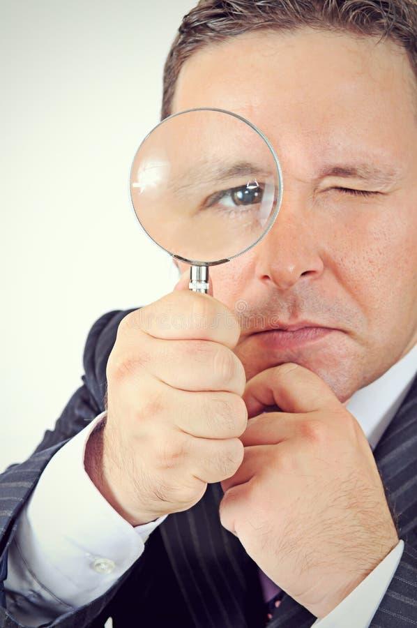Homme d'affaires dans un procès regardant par une loupe image libre de droits