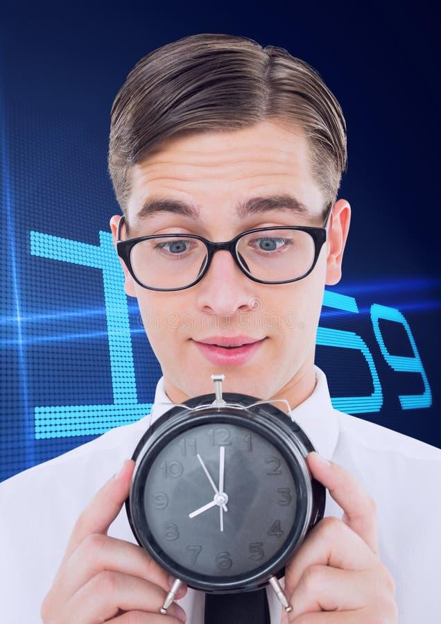 Homme d'affaires de ballot tenant une horloge sur le fond avec l'horloge images stock