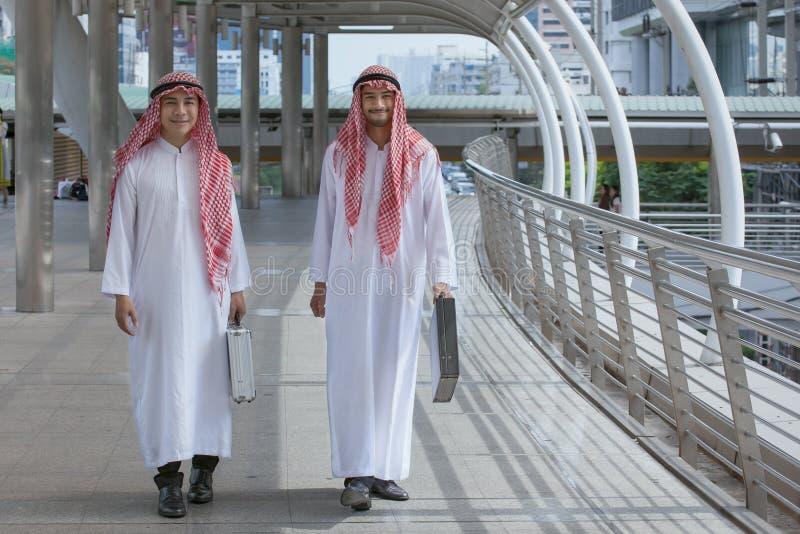 Homme d'affaires de deux Arabes avec la serviette et la promenade ensemble autour photo stock