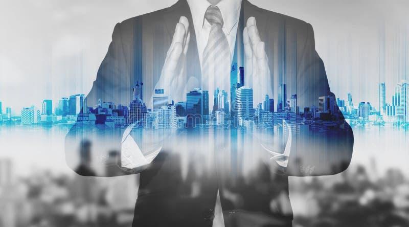 Homme d'affaires de double exposition tenant l'hologramme bleu de ville, technologie d'entreprise immobilière photos libres de droits