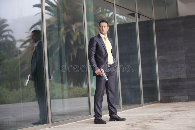 Homme d'affaires de garantie avec un pistolet photographie stock libre de droits