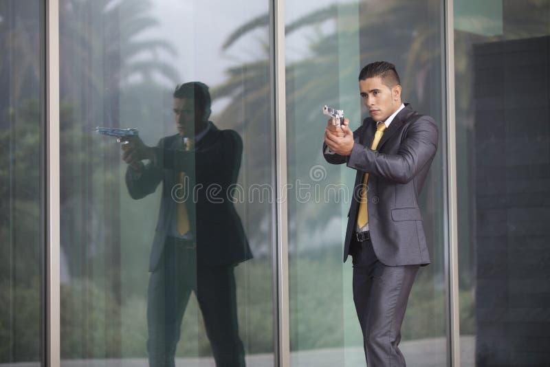 Homme d'affaires de garantie avec un pistolet photo stock