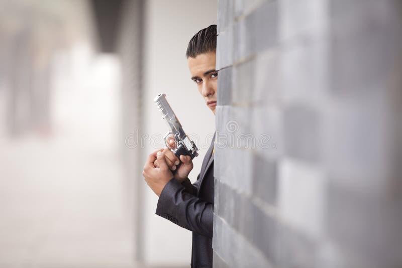 Homme d'affaires de garantie avec un pistolet image libre de droits