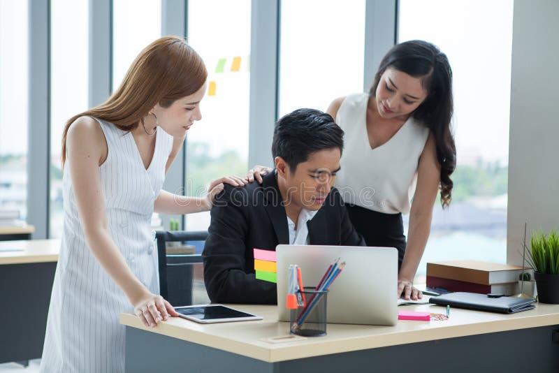 Homme d'affaires de gestes et de consolation de femme d'affaires dans le bureau l'employé de fille de travail d'équipe tapotant d photo libre de droits