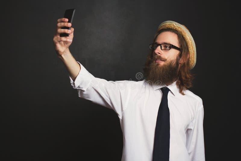 Homme d'affaires de hippie avec les verres et le chapeau prenant des autoportraits photos stock