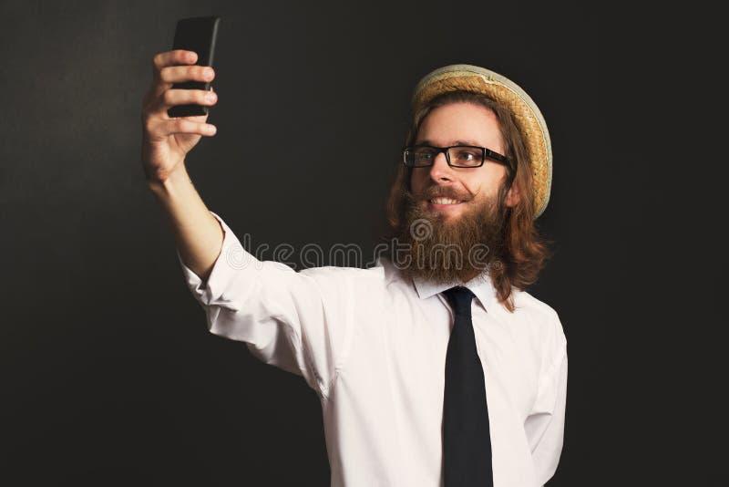 Homme d'affaires de hippie avec les verres et le chapeau prenant des autoportraits photographie stock