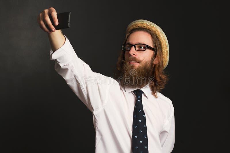 Homme d'affaires de hippie avec les verres et le chapeau prenant des autoportraits image stock